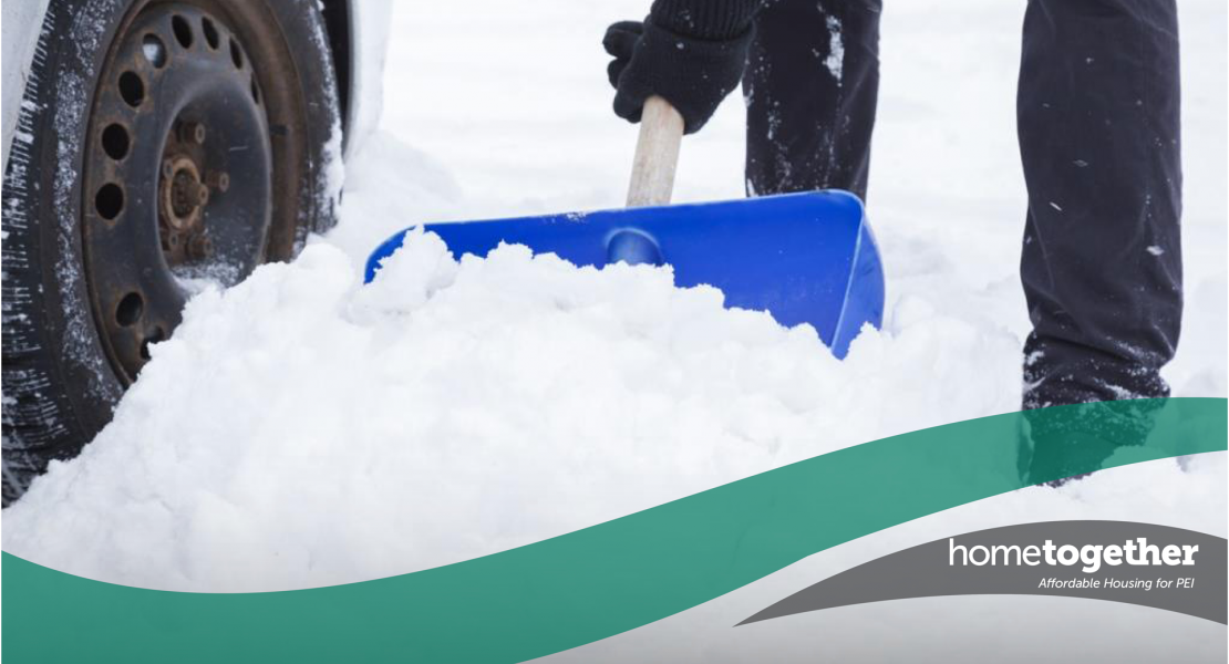 Stock image of individual shovelling snow near a car