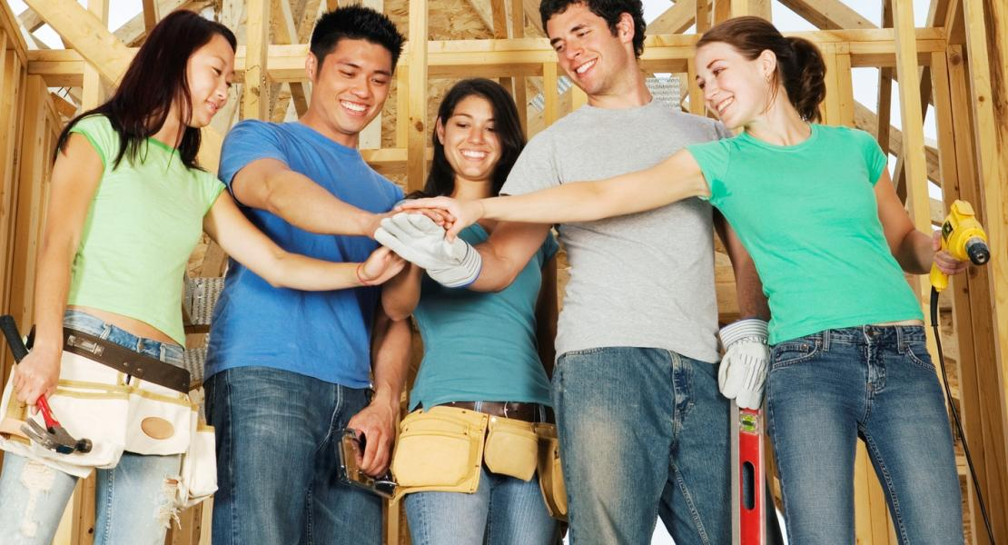Stock image of volunteers with hands together at construction site