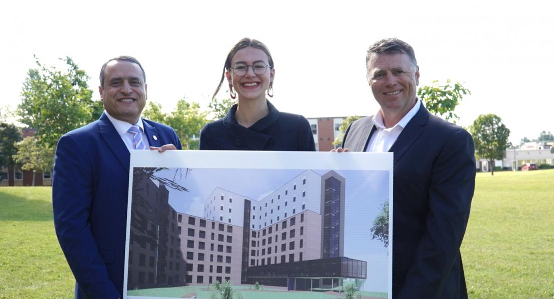 UPEI president, Dr. Alaa Abd-El Aziz, UPEI Student Union president Emma Drake and Premier Dennis King hold a rendition of the new 260 bed student residence at UPEI.